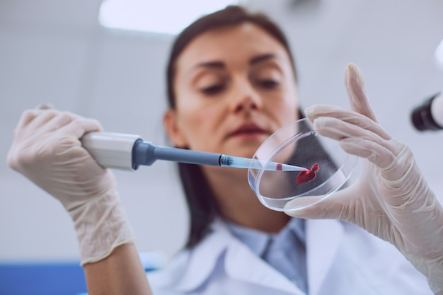 Świetne wyniki. odnoszący sukcesy inteligentny naukowiec przeprowadzający badanie krwi i noszący mundur