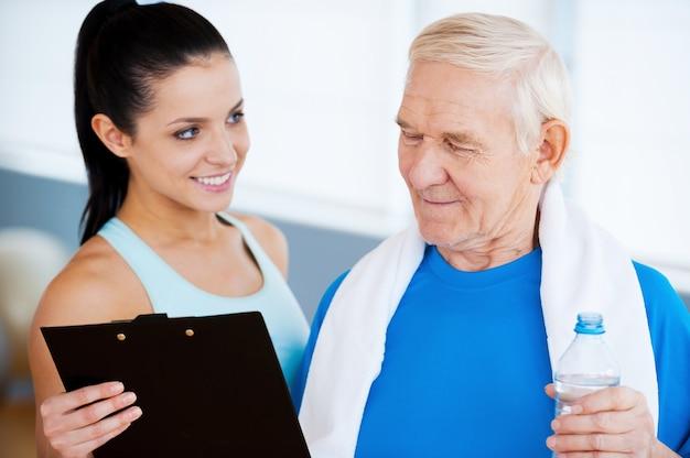 Świetne wyniki! pewny siebie trener osobisty stojący blisko starszego mężczyzny i pokazujący coś w swoim schowku