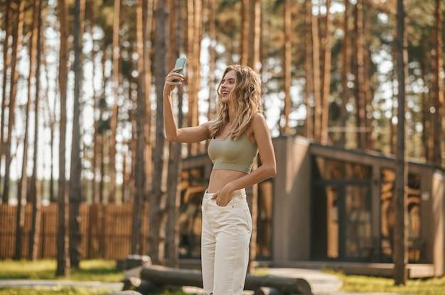 Świetne zdjęcie. przystojna młoda radosna kobieta w zwykłych ubraniach, biorąca selfie na zewnątrz w strefie rekreacyjnej w słoneczny jesienny dzień