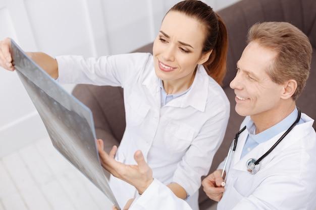 Świetnie ci poszło. dwóch prominentnych, przyjaznych pracowników medycznych znajduje konsensus w sprawie diagnozy i omawia leczenie podczas oglądania skanów mri pacjentów