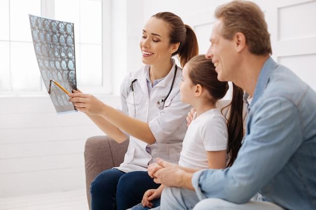 Świetnie się spisałeś. uśmiechnięty dość wybitny lekarz wyglądający na zachwyconego, wskazujący na skan mózgu i wskazujący na oznaki znacznej poprawy