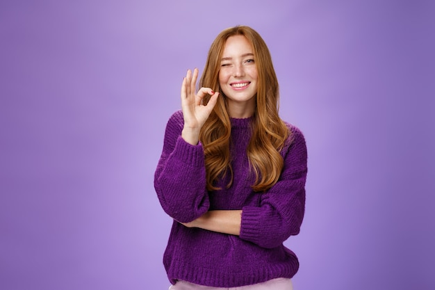 Świetnie się spisałeś. zadowolona i szczęśliwa, urocza, asertywna i wspierająca rudowłosa kobieta w fioletowym swetrze, uśmiechnięta i mrugająca z aprobatą pokazując dobry gest, lubiąca produkt na fioletowej ścianie.