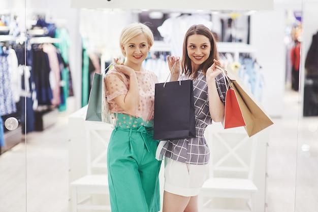 Świetny dzień na zakupy. dwie piękne kobiety z torbami patrząc na siebie z uśmiechem podczas spaceru w sklepie odzieżowym.