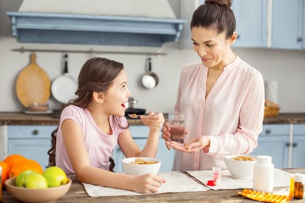 Świetny dzień. piękna, żywiołowa ciemnowłosa młoda matka uśmiecha się i podaje witaminy swojej córce i dziewczynie, jedząc śniadanie i siedząc przy stole