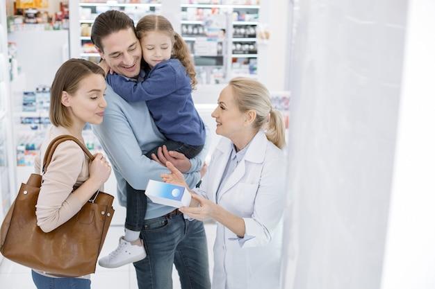 Świetny lek. pozytywna rodzina słuchająca farmaceutki i wpatrująca się w dół