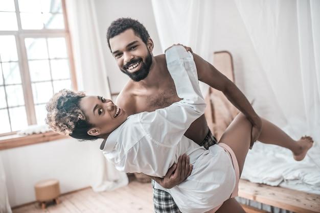 Świetny nastrój. atrakcyjny młody dorosły uśmiechający się african american tulenie kobieta w białej koszuli w tańcu ruchu w domu