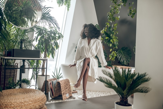 Świetny nastrój. ciemnoskóra młoda dorosła radosna kobieta w białej szacie boso siedząca w pobliżu roślin w spa