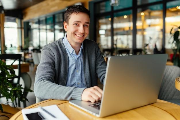 Świetny nastrój do pracy. przystojny młody człowiek pracuje na jego laptopie