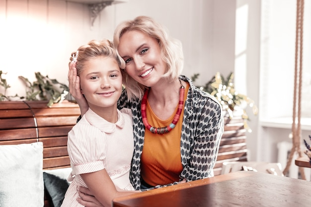 Świetny nastrój. radosna pozytywna mama i córka uśmiechają się do ciebie siedząc razem