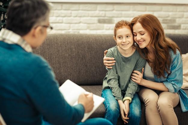 Świetny nastrój. zachwycona miła kobieta przytula córkę i wyraża swoje pozytywne emocje