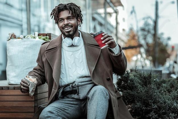 Świetny nastrój. zadowolony mężczyzna trzyma uśmiech na twarzy, trzymając w lewej ręce papierowy kubek