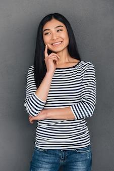 Świetny pomysł! piękna młoda azjatka trzymająca rękę na brodzie i odwracająca wzrok z uśmiechem