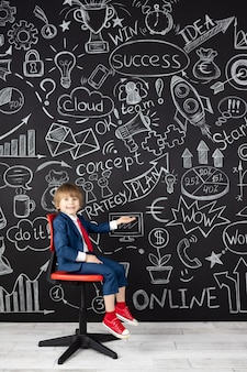 Świetny pomysł! śmieszne dziecko uczeń w klasie na czarnej tablicy. szczęśliwy dzieciak udawać biznesmena. koncepcja edukacji online i e-learningu. powrót do szkoły