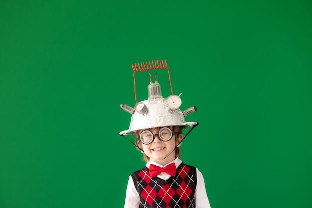 Świetny pomysł! śmieszne dziecko uczeń w klasie. szczęśliwe dziecko przed zieloną tablicą. koncepcja edukacji online i e-learningu. powrót do szkoły. koncepcja edukacji, uruchamiania i pomysłu na biznes start