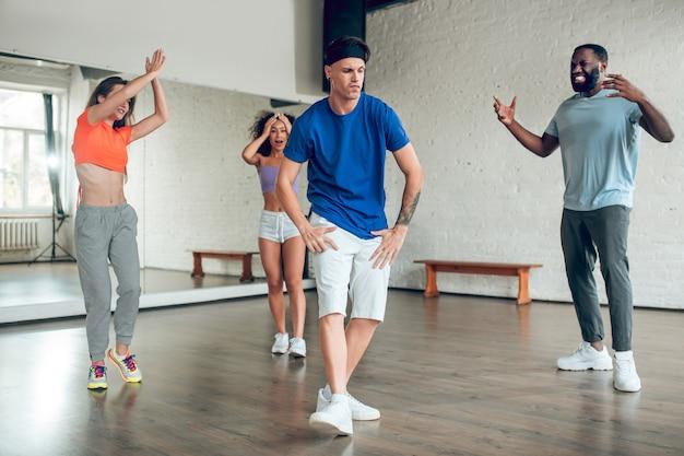 Świetny ruch. młody chłopak w opasce w koszulce i szortach tańczy z przyjaciółmi