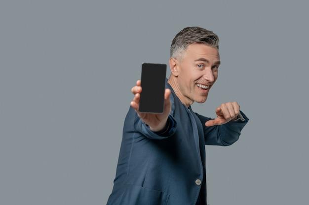 Świetny smartfon. szczęśliwy człowiek otimistin w kurtce biznesowej pokazujący ekran smartfona i wskazujący palcem na szarym tle