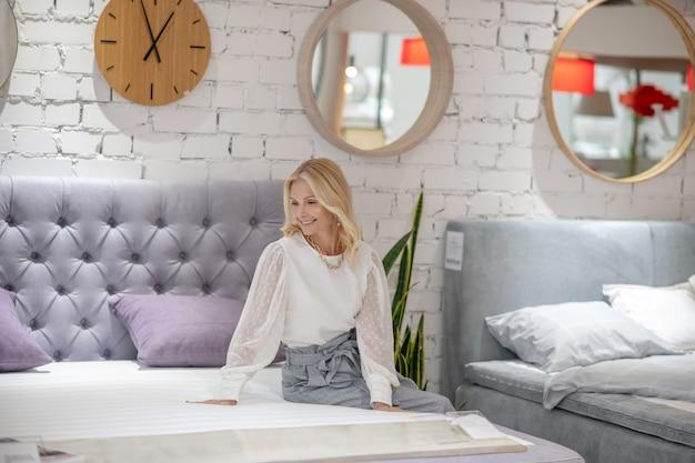 Świetny wybór. blondyn kobieta z biżuterią na szyi siedzi na nowym łóżku, patrzy z entuzjazmem, szczęśliwa.