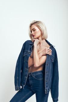 Świetny wygląd seksowna młoda kobieta w dżinsach nosi zamknięte oczy, stojąc na tle szarości