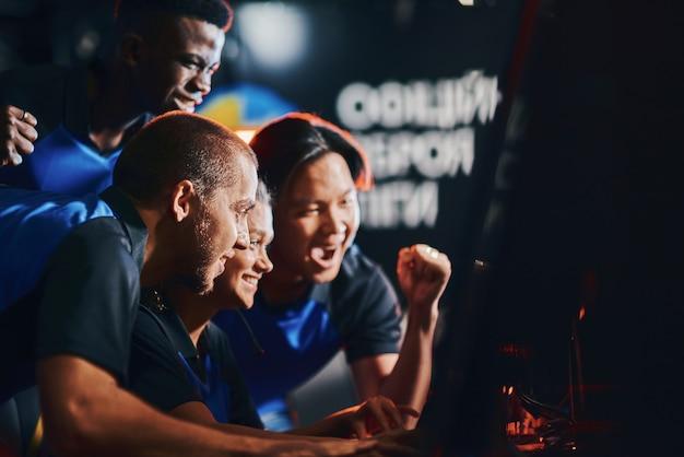 Świetny wynik. zespół podekscytowanych profesjonalnych graczy cybersportowych patrzących na ekran komputera i świętujących sukces podczas udziału w turnieju esportowym. granie w gry wideo online