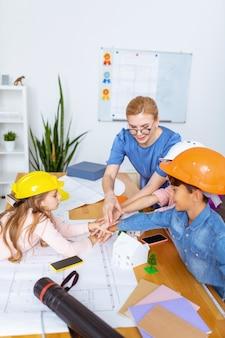 Świetny zespół. nauczyciel i uczniowie cieszący się pracą w świetnym zespole po modelowaniu smart city