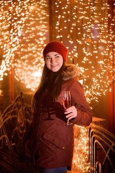 Święto bożego narodzenia. dziewczyna pije szampana nad wakacyjnym rozjarzonym złotym tłem.