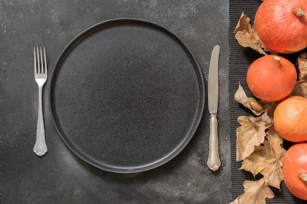 Święto dziękczynienia lub halloween miejsce ustawienia z dyni na czarny stół. widok z góry.