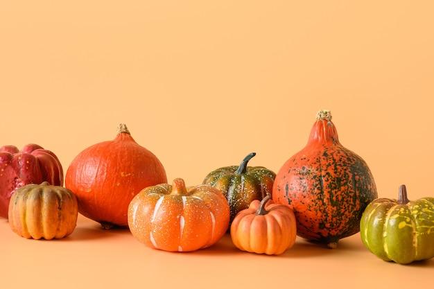 Święto dziękczynienia lub halloween różne zbiory dyni na pomarańczowym tle.