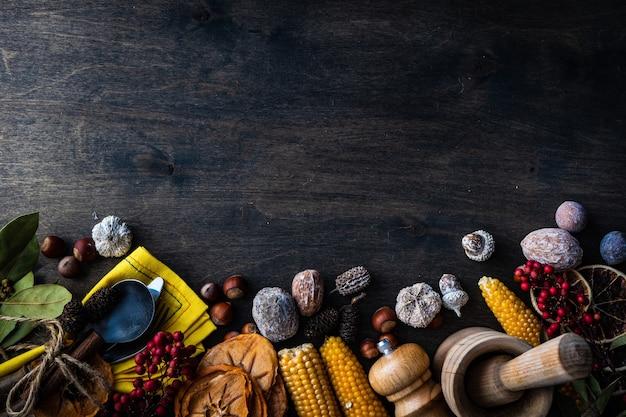 Święto dziękczynienia lub koncepcja jesiennych zbiorów z ramą z orzechami, jagodami, warzywami i owocami na ciemnej powierzchni drewnianej z miejsca na kopię