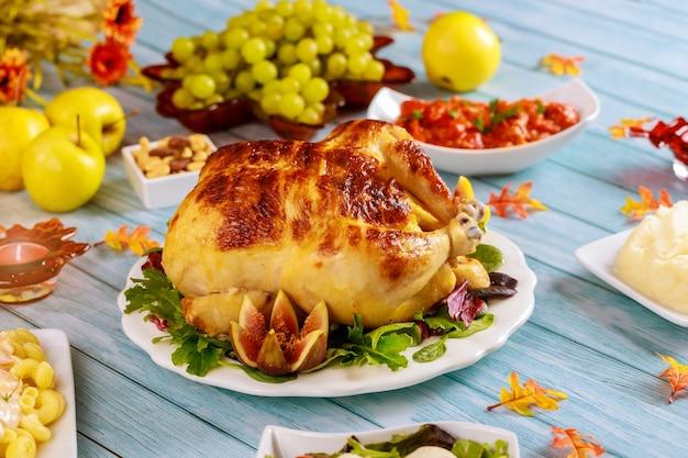 Święto dziękczynienia z indykiem lub kurczakiem podawane z ziemniakiem i jabłkiem na niebieskim drewnianym stole