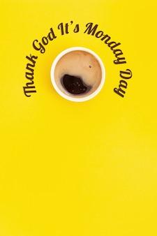 Święto - dzięki bogu jest poniedziałek. nagłówek i filiżanka kawy. widok z góry na żółtym tle.