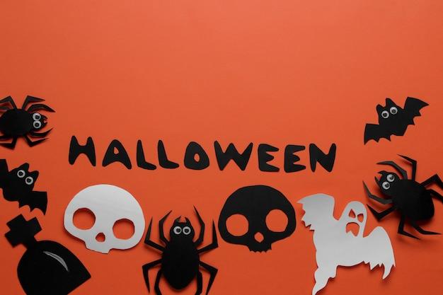 Święto halloween. kompozycja z różnymi figurami papieru halloween. widok z góry. na pomarańczowym tle