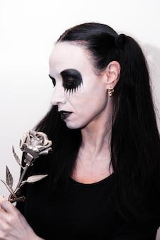 Święto halloween, portret dziewczynki z makijażem trzymającej metaliczny kwiat róży.