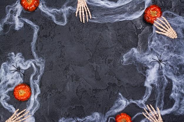 Święto halloween z rękami szkieletów, dyniami, pająkami i pajęczyną na czarno