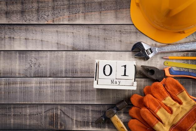 Święto pracy, drewniany blokowy kalendarz z wiele przydatnymi narzędziami na drewnianym tle
