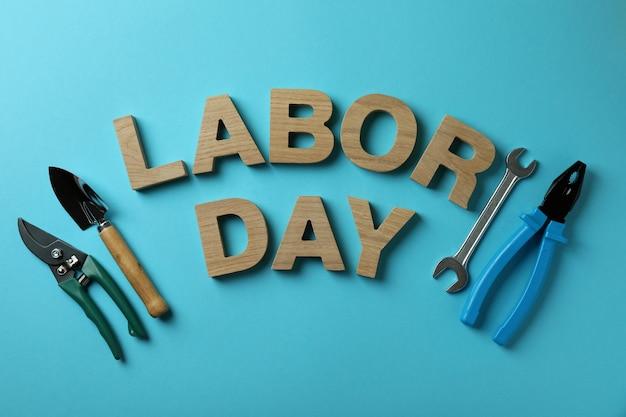 Święto pracy wykonane z drewnianych liter i narzędzi roboczych na niebiesko