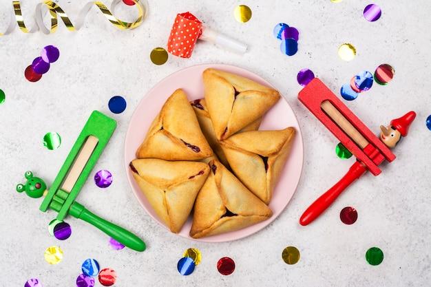 Święto purim. żydowski karnawał. tradycyjne żydowskie ciasteczka hamantaschen i akcesoria purim masquerade na jasnym tle