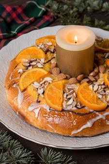Święto trzech króli jedzenie z plasterkami pomarańczy z zapaloną świecą z bliska