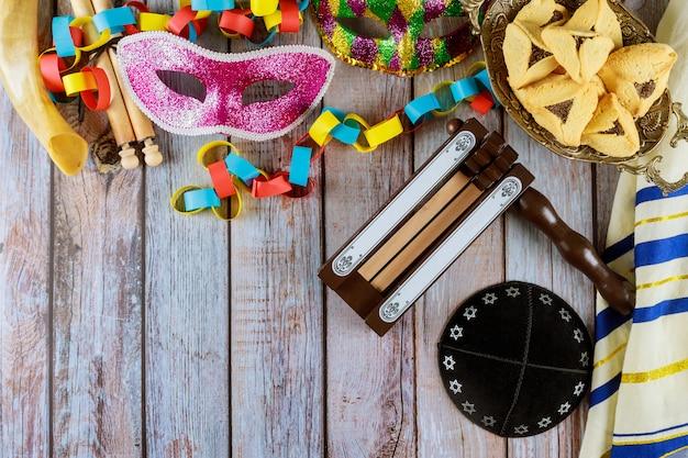 Święto żydowskiego karnawału purim z ciasteczkami hamantaschen, noisemaker i maska z pergaminem