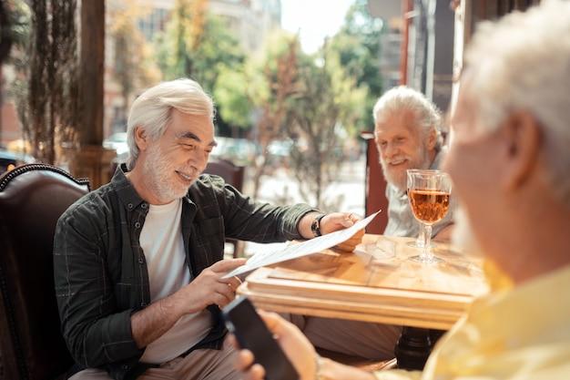 Świętowanie spotkania. trzech emerytów świętuje swoje spotkanie po wiekach, ale wcześniej wybierało drinki
