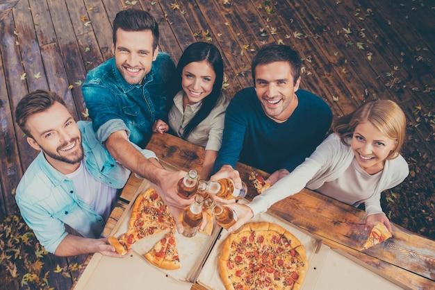 Świętowanie tego dnia. widok z góry pięciu szczęśliwych młodych ludzi, którzy stukają się szklankami z piwem i patrzą w kamerę, stojąc na zewnątrz