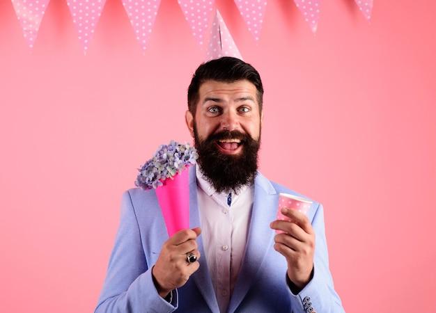 Świętowanie urodzin. uśmiechnięty brodaty mężczyzna w partyjnym kapeluszu z bukietem kwiatów.