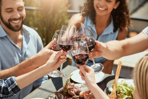 Świętująca przyjaźń grupa szczęśliwych młodych ludzi je świeże jedzenie, rozmawiając i brzęcząc