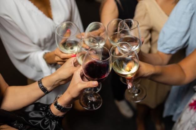 Świętujący ludzie trzymający kieliszki białego wina wznoszący toast