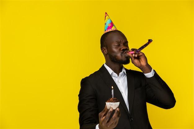 Świętujemy afrykańskiego mężczyznę trzymającego ciasto i gwizdy