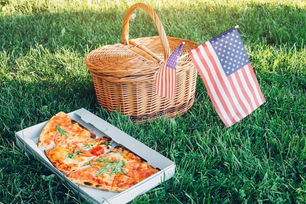 Świętujemy dzień niepodległości ameryki pizzą. kosz picknick z flagą usa.