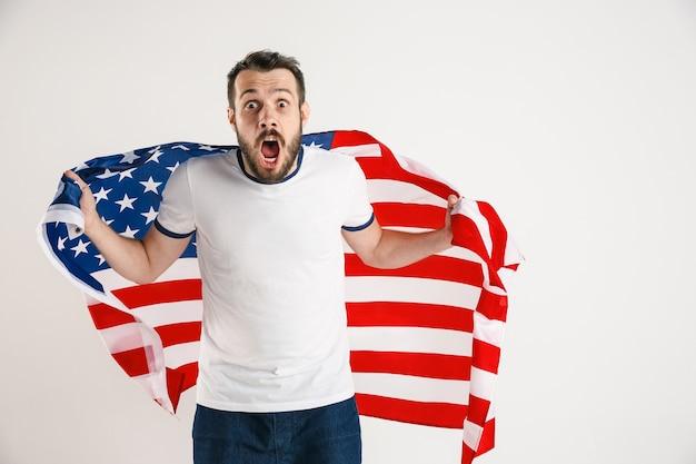 Świętujemy dzień niepodległości. gwiazdy i paski. młody człowiek z flagą stanów zjednoczonych ameryki na białym tle na ścianie białego studia. wygląda na szalenie szczęśliwego i dumnego jako patriota swojego kraju.
