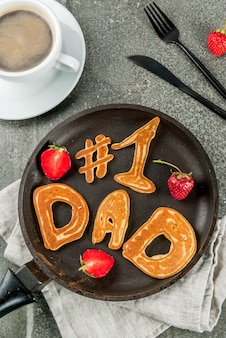 Świętujemy dzień ojca. śniadanie. pomysł na obfite i pyszne śniadanie: naleśniki w formie gratulacji - tata nr 1. na patelni, kubku do kawy i truskawkach. widok z góry copyspace