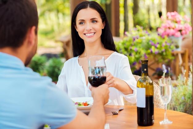 Świętujemy ich miłość. piękna młoda kochająca para opiekająca czerwone wino i uśmiechnięta podczas wspólnego relaksu w restauracji na świeżym powietrzu