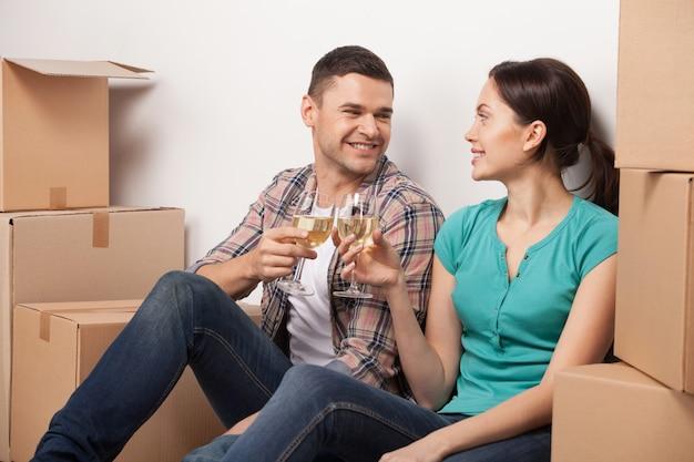 Świętujemy ich przeprowadzkę do nowego mieszkania. wesoła młoda para siedzi na podłodze i pije wino, podczas gdy wokół nich leżą kartony