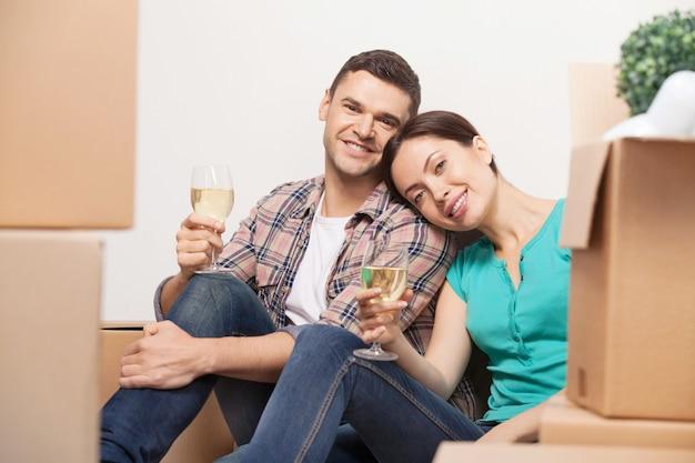 Świętujemy ich przeprowadzkę. piękna młoda para siedzi na podłodze i pije wino, podczas gdy wokół nich leżą kartony